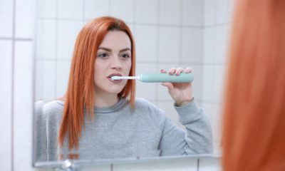 This picture show a woman brushing her teeths.