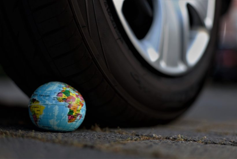 This picture show a tire on top of the earth globe.