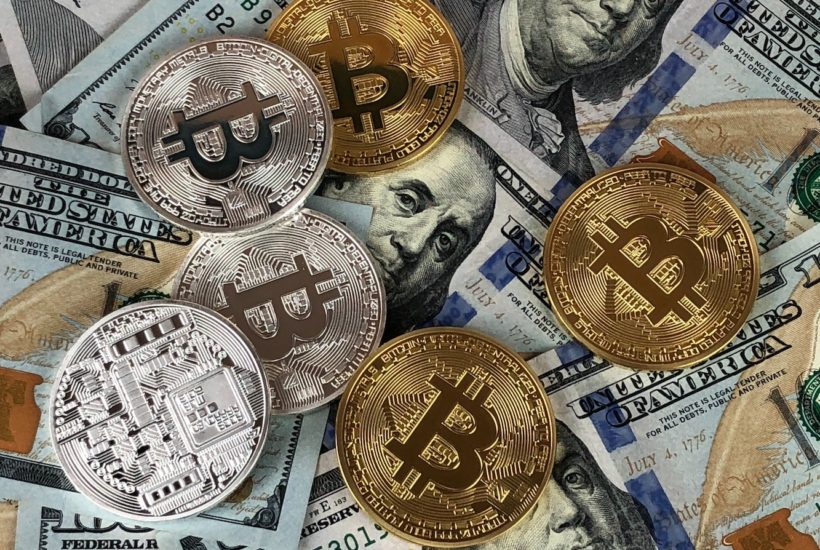 This picture show a bunch of cryptocoins in top of some dollars.