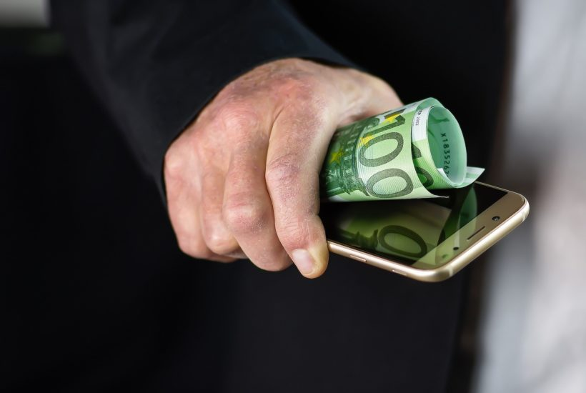This picture show a person holding a phone and a dolar bill.