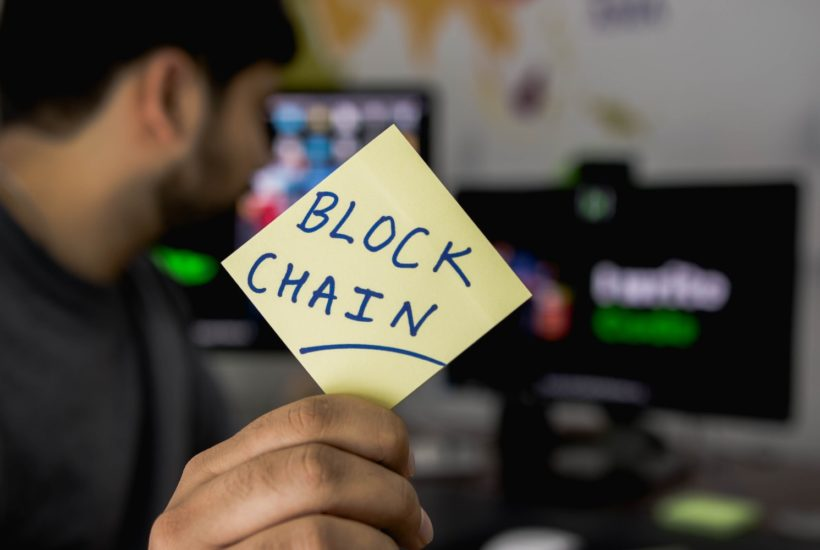 This picture show a person holding a blockchain sign.