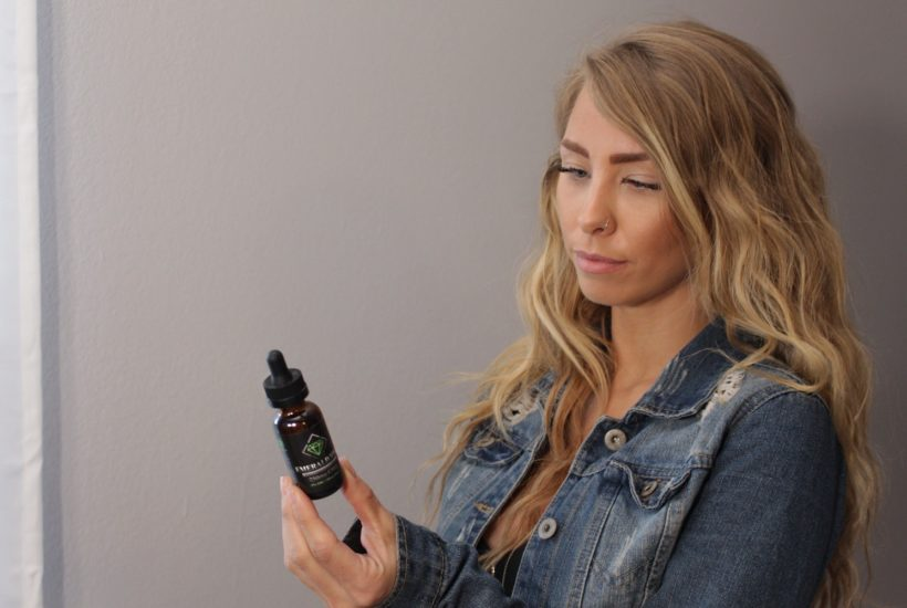 This picture show a person looking at a CBD oil.